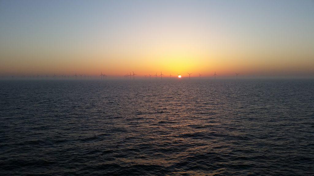 Un champ d'éolienne en mer avec un coucher de soleil