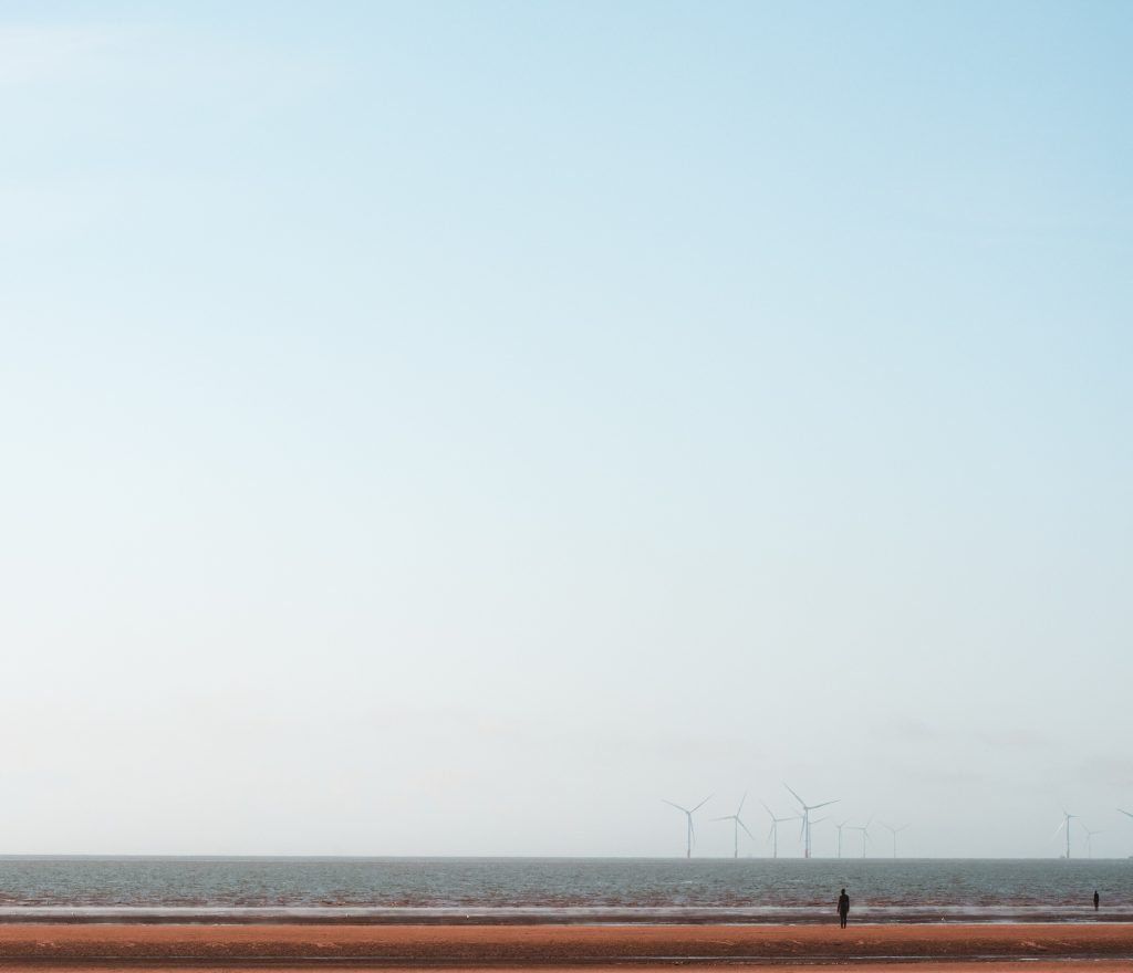 une plage avec un champt d'éoliennes au loin
